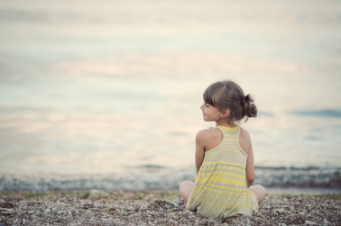 little girl meditating on the beach